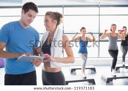 Trainer presenting timetable while aerobics class lifting weights in gym - stock photo