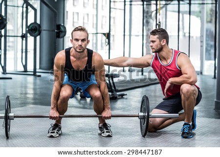 Trainer supervising a muscular man lifting a barbell - stock photo