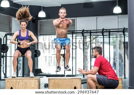 Trainer supervising muscular athletes doing jumping squats - stock photo