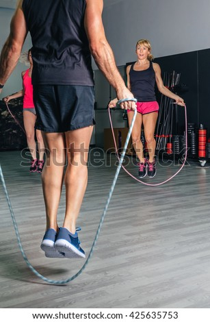 Trainer teaching exercises with jumping ropes to women - stock photo