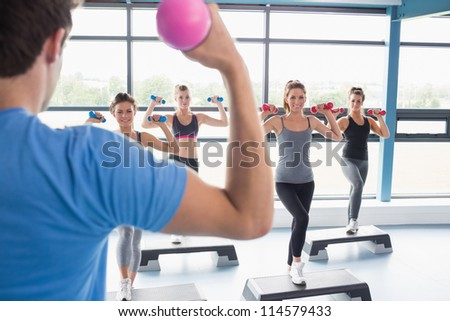 Trainer teaching his aerobics class while lifting weights in gym - stock photo