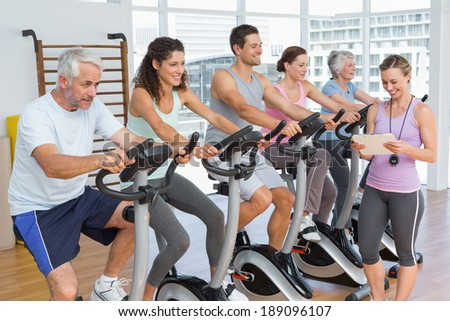 Trainer walking along people working out at elypticalclass in gym - stock photo
