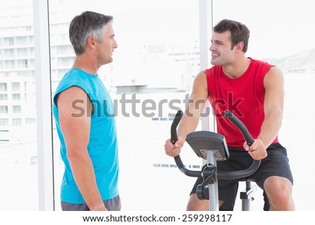 Trainer with man on exercise bike in fitness studio - stock photo