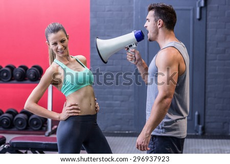 Trainer yelling through the megaphone to a muscular woman - stock photo