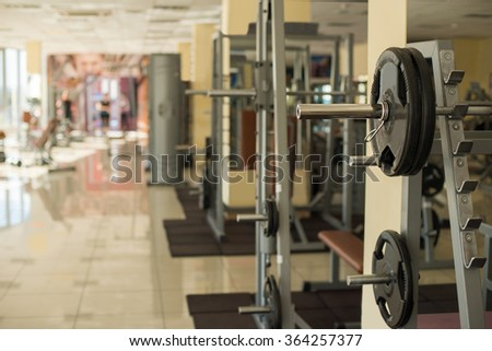 Trainers in gym hall. Barbells hanging on metal rack in gym hall. Different apparatus on the background. - stock photo