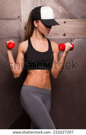 Training every day! Beautiful young woman in cap holding dumbbells while standing against metal background - stock photo