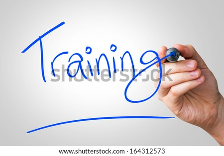 Training hand writing with a blue mark on a transparent board - stock photo
