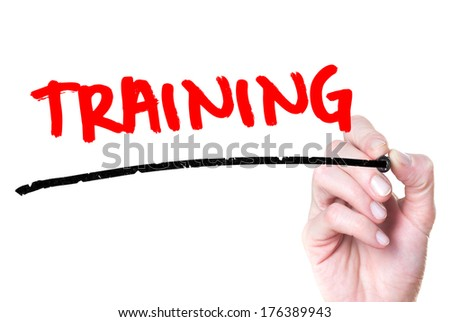 Training hand writing with a red mark on a transparent board - stock photo