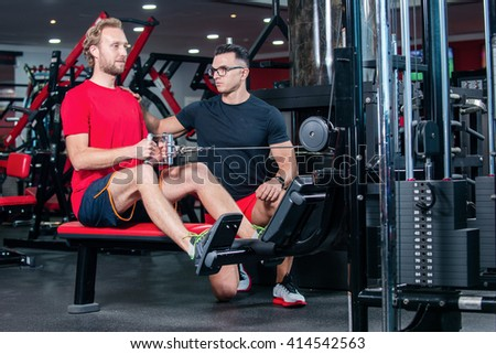 Training in the gym with trainer. Confident coach shows the customer how to do the training in the gym on the simulator. - stock photo