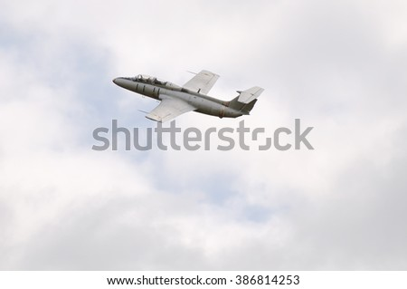 Training jet aircraft flying in cloudy sky - stock photo