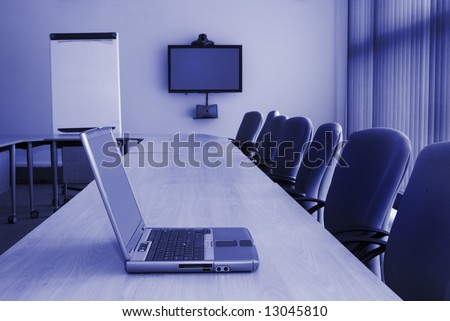 Training room with desk chairs laptop video conferencing equipment and white board - stock photo