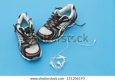 Training shoes and headphones on a blue yoga mat - stock photo