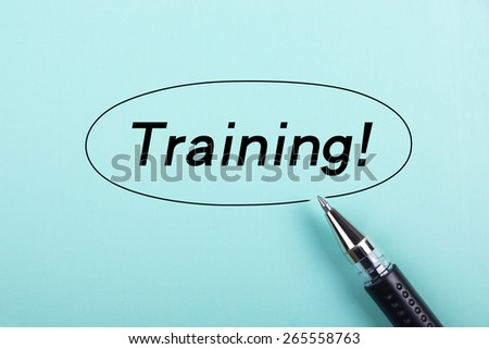 Training text is on blue paper with black ball-point pen aside. - stock photo