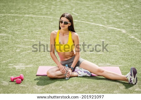 Training with dumbbells. Girl with dumbbells sitting on the field and drinking water - stock photo