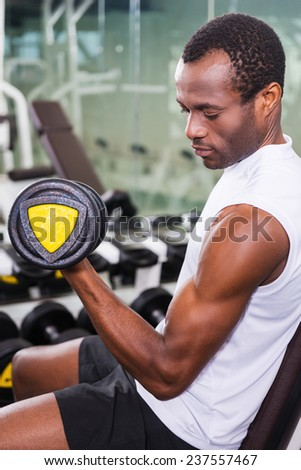 Training with dumbbells. Handsome young African man training with dumbbell in gym - stock photo