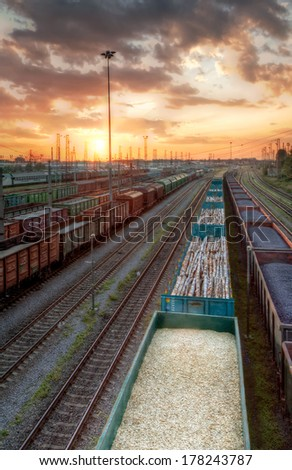 Trains shipping coal, splint and macadam at sunset (in High Dynamic Range) - stock photo