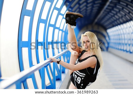 Trains young girl stretching at the ballet school. Girl wearing hip-hop style sit on twine - stock photo