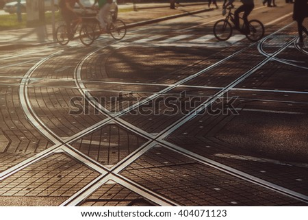 Tram lines intersection on paved street in Zagreb, Croatia, intentionally blurred background with people going from work, bicyclists, commuters - stock photo