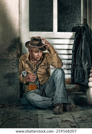 Tramp man smoking and drinking alcohol. Lonely vagabond in depression - stock photo