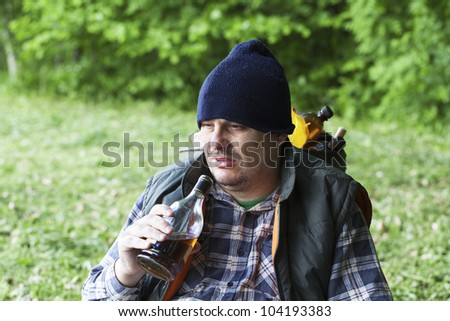 Tramp sitting in the park and drinking alcohol - stock photo