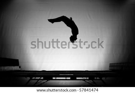 trampoline silhouette somersault - stock photo