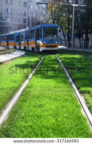 Tramway running on rails surrounded by fresh green grass in city center - stock photo