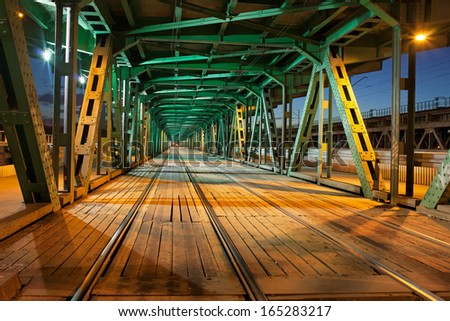 Tramway with two tracks in the lower part of the steel truss Gdanski Bridge in Warsaw, Poland, night illumination, vanishing point perspective. - stock photo