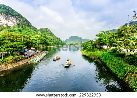 TRANG AN ECO-TOURISM SITE, NINHBINH, VIETNAM - NOVEMBER 2, 2014 - Visitors start their voyage along for sightseeing. This location is very famous for beautiful landscape. It's a UNESCO heritage site. - stock photo