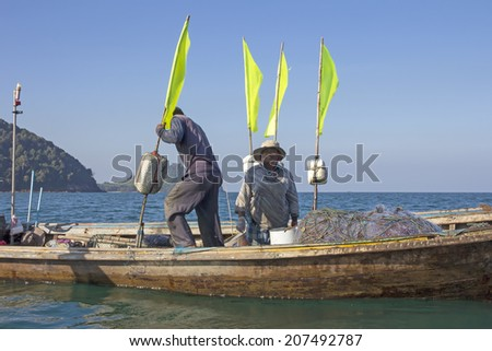 Trang Province, Thailand-March 7th 2014: A Thai fisherman and his wife at work in the Andaman Sea. Fishing provides a livelihood for many people in Thai coastal areas. - stock photo