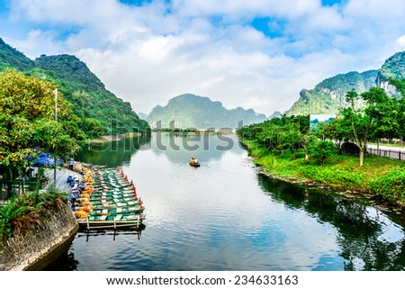 TRANGAN ECO-TOURIST COMPLEX, VIETNAM - NOVEMBER 27, 2014 - View of entrance of the Complex with boats waiting. This is a UNESCO site and very famous for its beauty of caves, temples & natural beauty. - stock photo