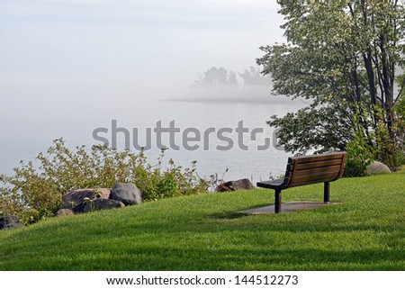 Tranquil bench on the foggy shore - stock photo