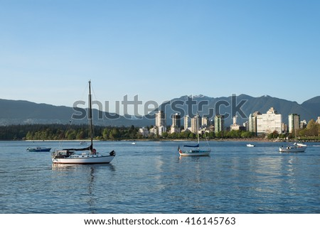 Tranquil evening time in Kitsilano Dog Beach, Vancouver, British Columbia, Canada. Sailing boats are resting on the ocean while looking at the city skyline in English Bay. - stock photo