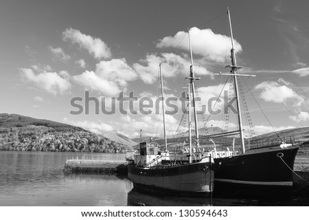 Tranquil harbour of Inveraray Scotland with nice cloudscape in black and white - stock photo