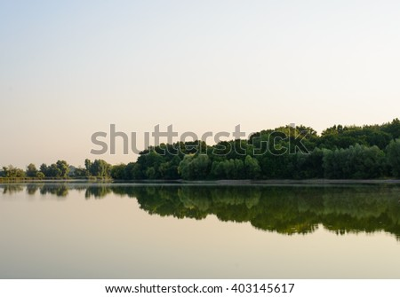 Tranquil lake with reflections of surrounding trees and bushes at dawn or dusk with a faint orange glow to the sky - stock photo