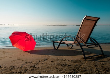 Tranquil Mediterranean morning beach with red umbrella and chair - stock photo