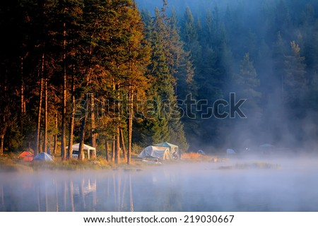 tranquil morning sunrise over the camp near bulgarian high mountain lake  - stock photo