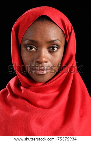 Tranquil portrait of beautiful young black woman wearing red hijab, taken against a black background. - stock photo