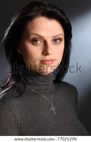 Tranquil portrait of beautiful young caucasian woman with bright green eyes, wearing a crucifix necklace. - stock photo