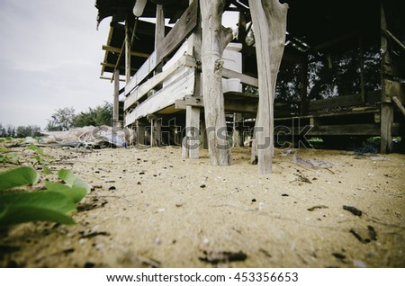 tranquil rural area near the seashore, wooden fisherman hut on the sandy beach. fish net and white ice box. - stock photo
