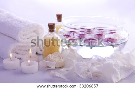 Tranquil scene, composed by candles, white towels, bath salts, soap bar, petals and a bowl with flowers floating on it. It has a lilac light. - stock photo