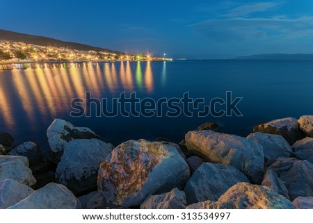 Tranquil scene of small town on Adriatic sea at night with stones in foreground.  - stock photo