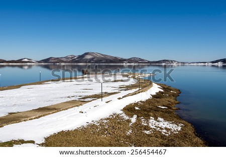 Tranquil scenery.Landscape,Black snowy mountain,clear sky and a water bike on lake at a winter day,Greece - stock photo