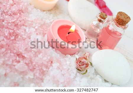 Tranquil spa relaxation setting pink white bath salt, candles, aroma essence bottles, spa stones. Soft focus - stock photo