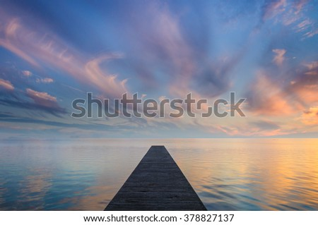 Tranquil symmetric shot of a jetty leading into a lake. Accompanied by an awesome sunset spectacle. - stock photo