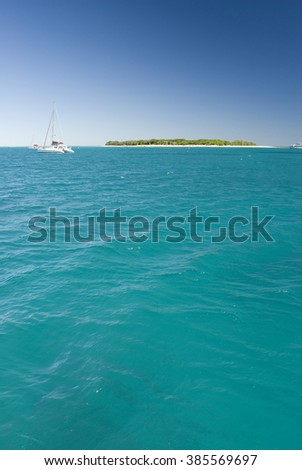 Tranquil tree lined island on green and blue ocean horizon with sailboat in foreground and copy space - stock photo