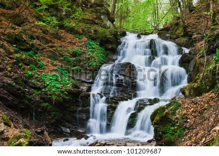 Tranquil waterfall scenery in the middle of autumn forest - stock photo