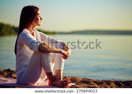 Tranquil young woman sitting on the beach - stock photo
