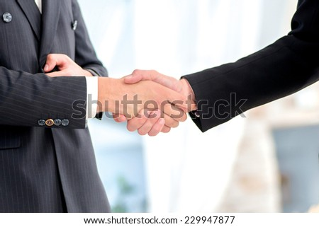 Transaction business. Two successful and confident businessman talking in office shaking hands with each other - stock photo