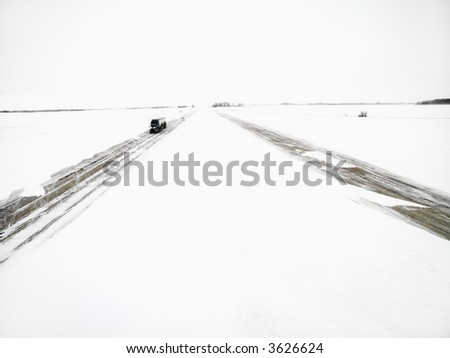 Transfer truck driving down highway in a winter storm. - stock photo