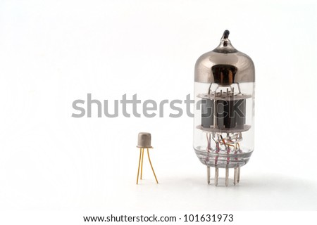 Transistor next to a vacuum tube on a white background - stock photo